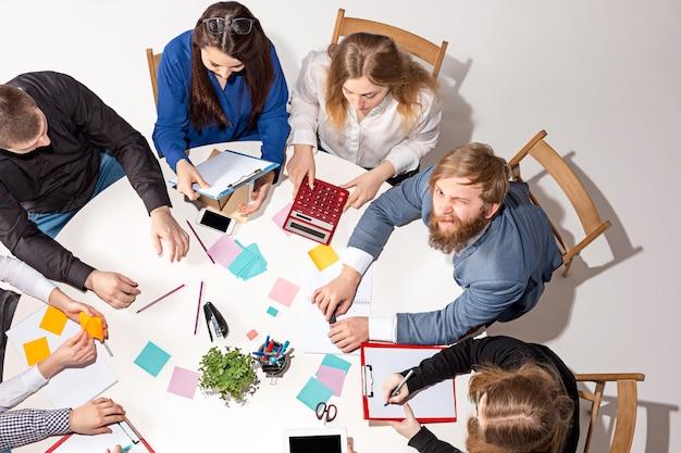 책상 뒤에 앉아, 보고서를 확인하고, 이야기하는 팀.
