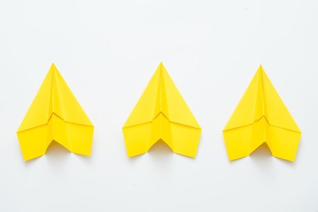 팀 정신과 야망. 세 개의 노란색 종이 비행기 화이트에 격리.