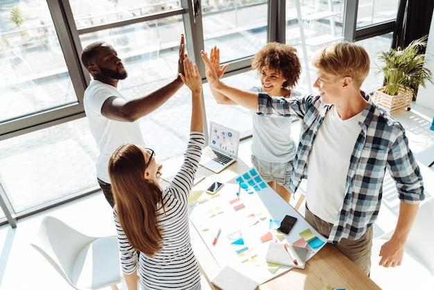 Командный дух. веселая молодая группа людей, дающих пять и наслаждающихся своей работой, стоя в офисе