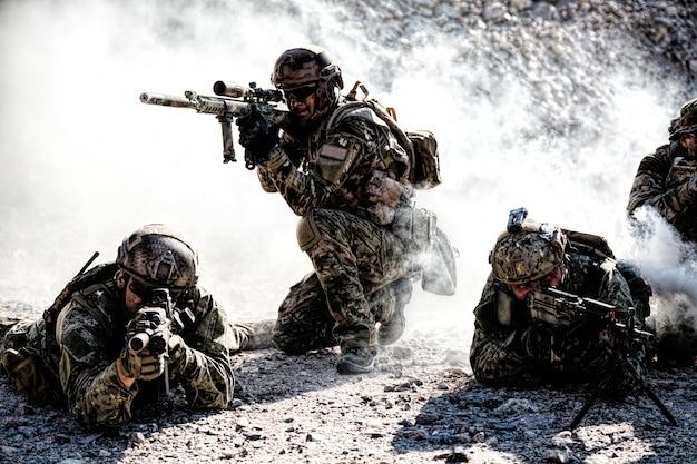 Отряд спецназа в действии в пустыне среди скал, покрытых дымовой завесой