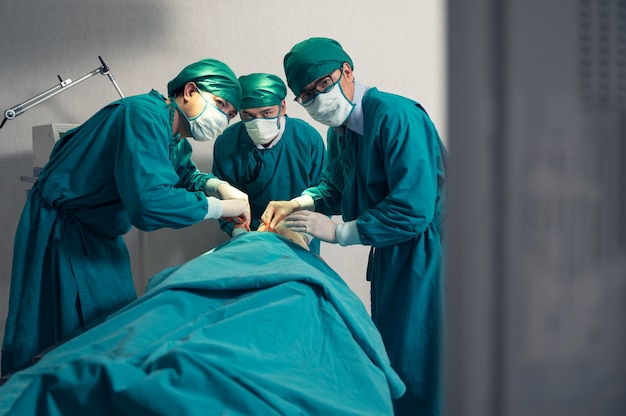 Team of surgeon in surgical gown operating accident patient and looking at monitor in operating room at hospital