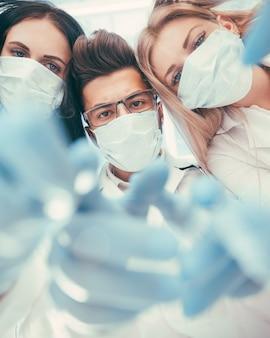 Хирурги бригады проводят операцию с использованием медицинских инструментов в современной операционной, вид снизу