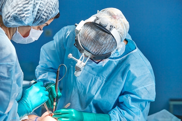 Team of surgeons makes an invasive operation