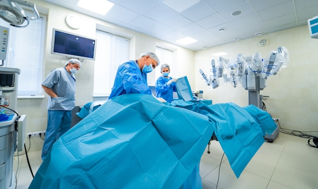 Team of surgeons performing operation in bright modern surgery room.