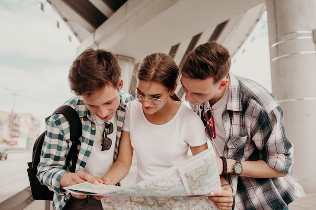 A team of teenage tourists carefully study the map together walking on a summer day around the city