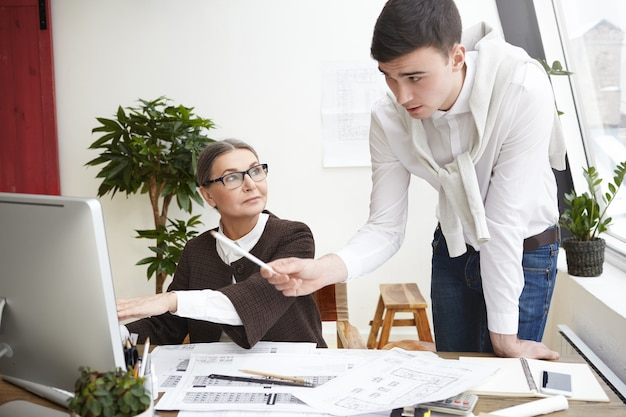 Team of two skillful architects young man and elderly woman developing new residential housing project, working on generic computer in office, using cad program, man pointing at screen with pencil