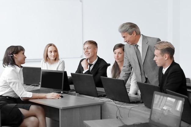 非公式の会議中にラップトップを使用するチーム