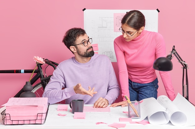 Team of woman and man discuss cooperative project look attentively at sketch cooperate for good teamwork pose at desktop in office against pink wall. entrepreneurship and cooperation concept