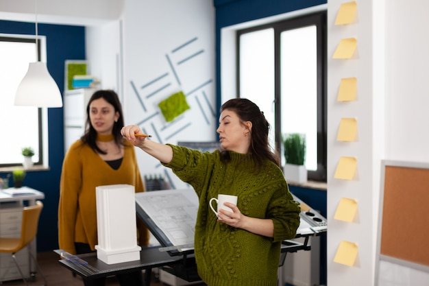 Team of women architects standing in creative agency office discussing and analysing building model measuring prototype with pencil