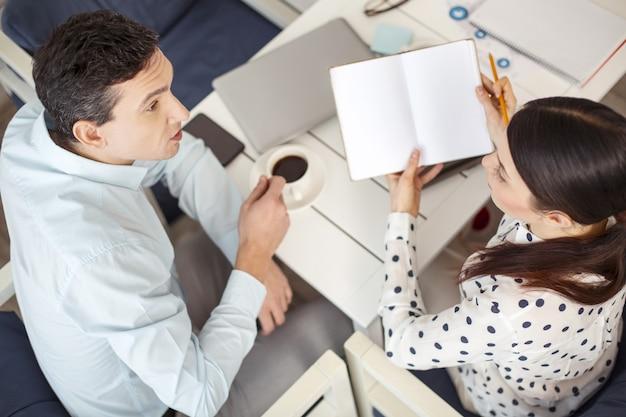 팀워크. 매력적인 집중 검은 머리 남자가 그 옆에 앉아 그의 여성 동료와 이야기하고 그녀는 노트북을 들고