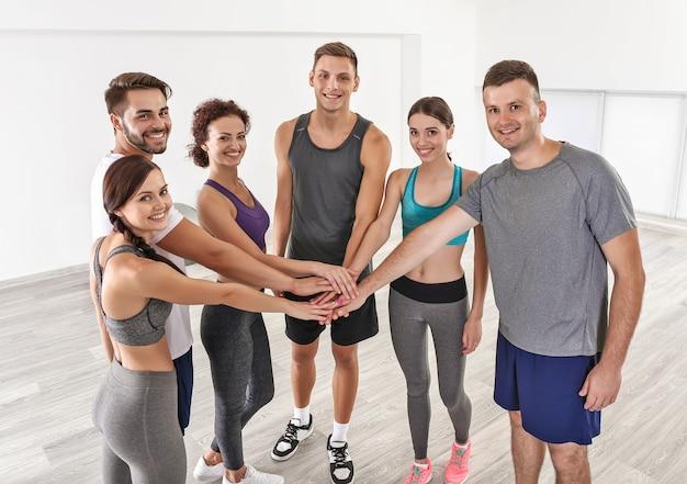 팀 작업 개념. 체육관에서 손의 더미를 만드는 사람들의 그룹