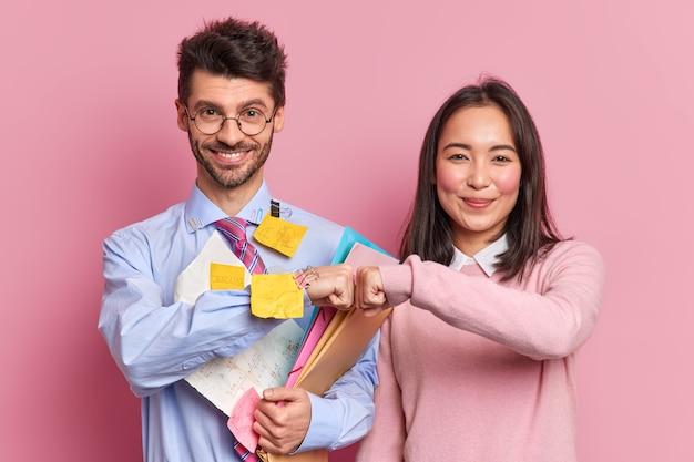 チームワークのコンセプト。幸せな多様なプロの同僚は、成功を達成し、タスクを完了するために喜んで紙とステッカーのメモで覆われた一般的なプロジェクトの仕事の人で一緒に拳バンプを動作させます。