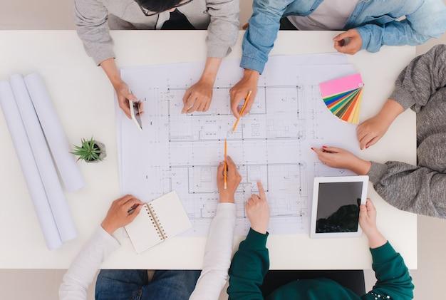 팀 작업 개념입니다. 인테리어 제작 프로젝트의 그래픽 계획을 그리는 남녀 건축가 동료