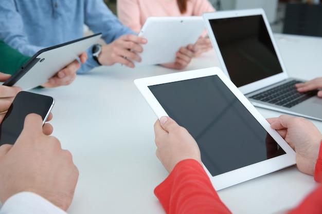 팀 작업 개념. 사무실 테이블에 앉아 디지털 장치를 사용하는 사람들