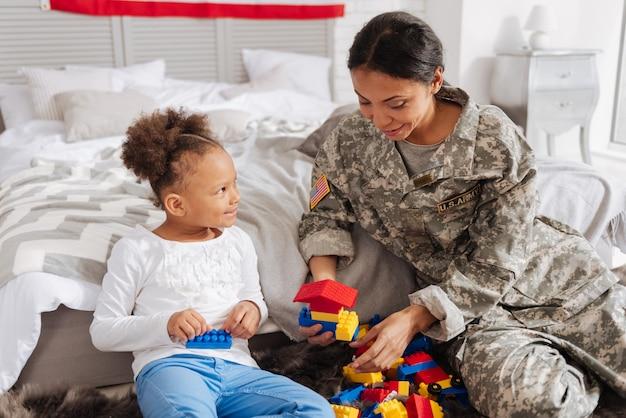 Совместная деятельность. великолепный эмоциональный энергичный ребенок, играющий со конструктором, собирающий шланги, пока мама проводит отпуск со своей семьей