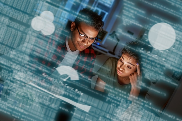 프로그래머의 팀 작업은 새 코드를 작성하고 있습니다. 젊은 남녀가 사용자 행동을 분석하고 있습니다.