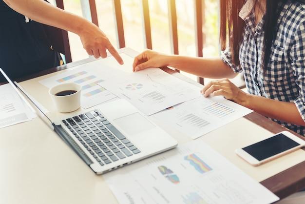 チームワークプロセス。オープンスペースのオフィスでラップトップと紙のグラフを持つ2人のビジネスウーマン。ビジネスコンセプト。