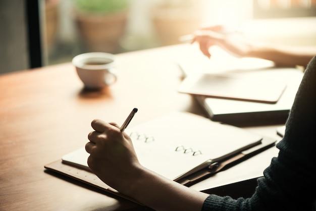 チームワークプロセス。若いビジネスマネージャーの乗組員が新しいスタートアッププロジェクトを手がけています。木製テーブルのラップトップ、キーボードの入力、メッセージのメッセージ、グラフプランの分析。レンズフレア。