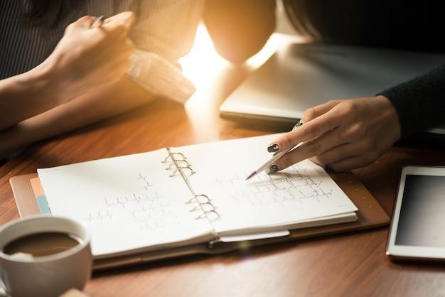 チームワークプロセス。若いビジネスマネージャーの乗組員が新しいスタートアッププロジェクトで働いています。木製テーブル上のラボ、キーボードの入力、メッセージのメッセージ、グラフプランの分析。レンズフレア。