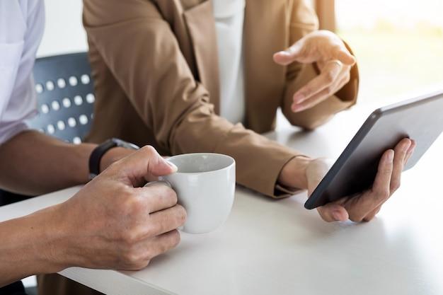 チームワークプロセス。新しいスタートアッププロジェクトで働く若いビジネスマネージャーのクルー。木製テーブルのラップトップ、キーボードの入力、メッセージのメッセージ、グラフプランの分析。