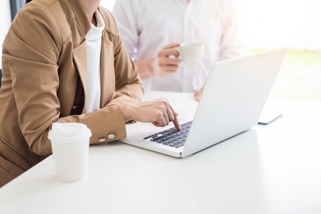 チームワークプロセス。若いビジネスマネージャーの乗組員が新しいスタートアッププロジェクトを手がけています。木製テーブルのラップトップ、キーボードの入力、メッセージのメッセージ、グラフプランの分析。