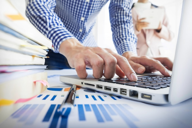 チームワークプロセス。若いビジネスマネージャーの乗組員が新しいスタートアッププロジェクトで働いています。木製テーブル上のラップトップ、キーボードの入力、メッセージのメッセージ、グラフプランの分析