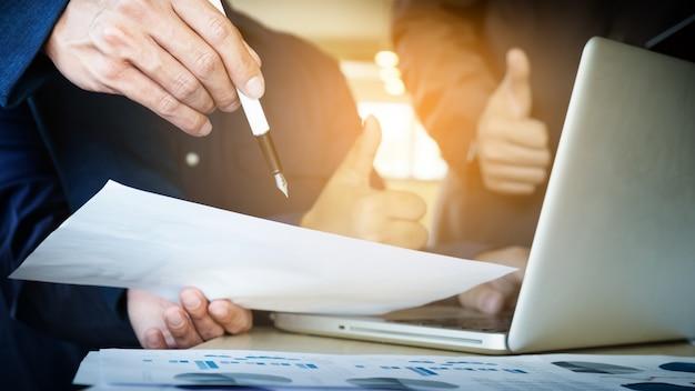 チームワークプロセス。若いビジネスマネージャーの乗組員が新しいスタートアッププロジェクトで働いています。木製テーブル上のラボ、キーボードの入力、メッセージのメッセージ、グラフプランの分析。