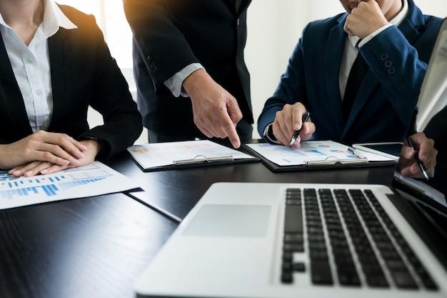チームワークプロセス。若いビジネスマネージャーの乗組員が新しいスタートアッププロジェクトを手がけています。木製テーブル上のノートパソコン、キーボードの入力、メッセージのメッセージ、グラフプランの分析