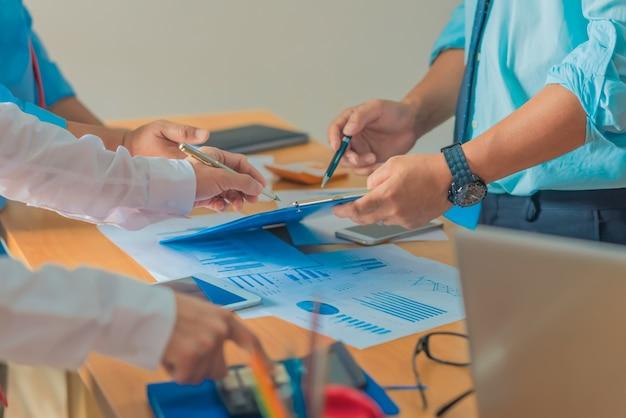 Командный процесс. молодой бизнес-менеджеры, работающие с новым проектом запуска. планшет на деревянном столе, ввод клавиатуры, текстовое сообщение, анализ графиков