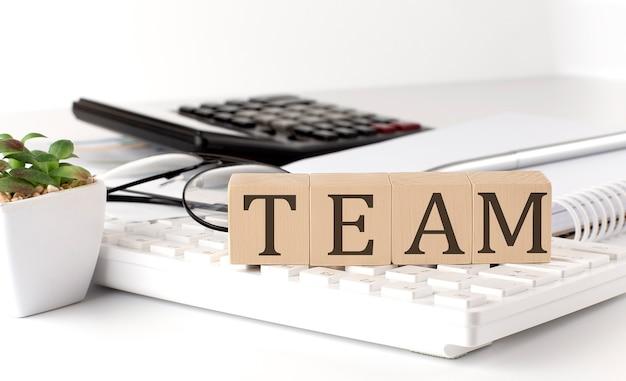 オフィスツールを使用してキーボードの木製の立方体に書かれたチーム