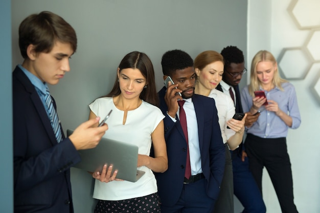 Team of young beautiful people in the office with mobile phones