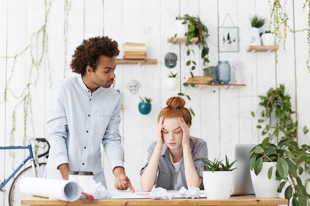 Team di giovani designer che affrontano la scadenza mentre si lavora al progetto architettonico in ufficio
