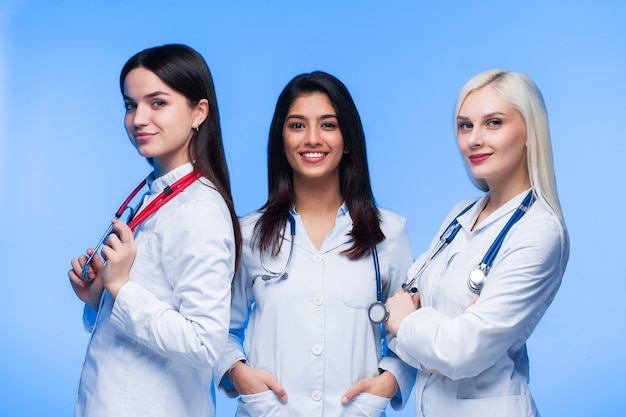 A team of young doctors. multinational people - doctor, nurse and surgeon in blue background. a group of medical students of different nationalities are looking in the cell.