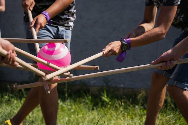 Teambuilding game for group of people for getting team spirit and increase friendship for colleagues. team game with ball and sticks