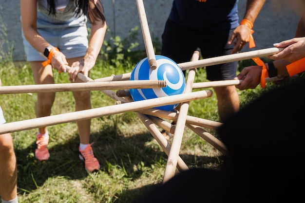 Teambuilding game for group of people for getting team spirit and increase friendship for colleagues. team game with ball and sticks.
