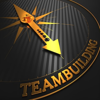 Teambuilding - golden compass needle on a black field pointing to the word