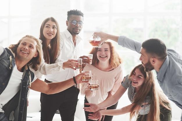 Товарищи по команде пьют виски и смеются из-за успешной сделки