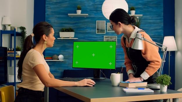 机のテーブルに座って、モックアップグリーンスクリーンクロマキーディスプレイを備えたコンピューターで作業するビジネスコミュニケーションについて話しているチームメート