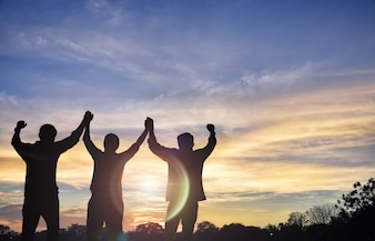 Команды, которые готовы поделиться успехом, стоят вместе, держат руки, смотрят на заход солнца