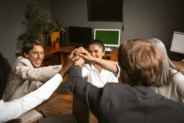 チームワーク。若いビジネスマンのグループが集まってプロジェクトを作成しました。現代のオフィスで若いフリーランサーのグループ握手
