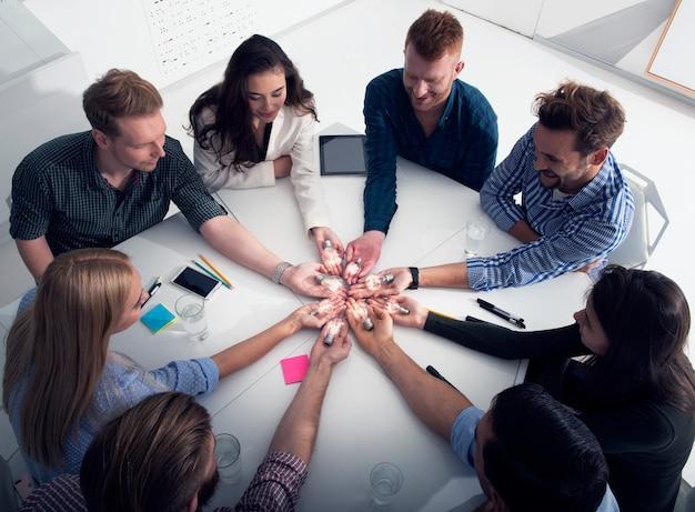 Концепция совместной работы и мозгового штурма с бизнесменами, которые разделяют идею с лампой. концепция стартапа компании