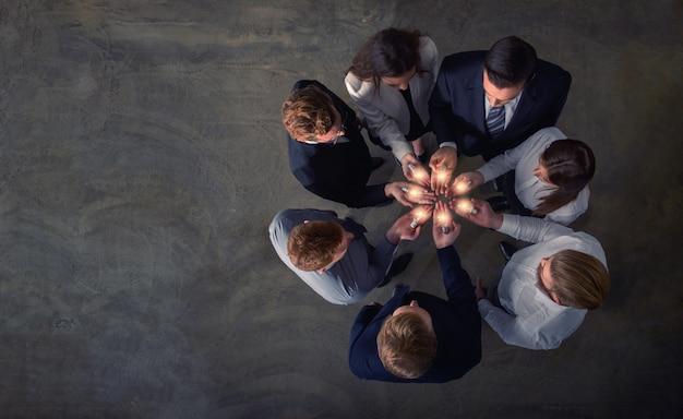 Концепция совместной работы и мозгового штурма с бизнесменами, которые разделяют идею с лампой. концепция стартапа