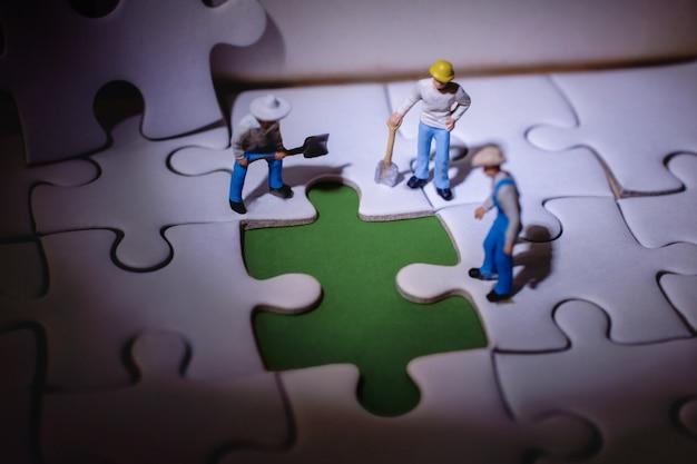 チームワークと問題解決の概念。ミニチュア労働者が何か間違ったことを発見
