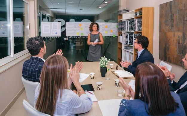 Работа в команде аплодирует женщине-руководителю на встрече, чтобы отпраздновать успех бизнес-проекта в штаб-квартире