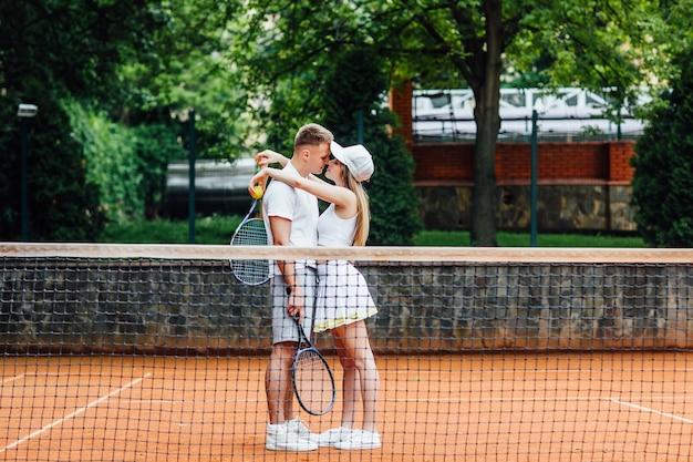 チームワーク。テニスをしている後の美女とハンサムな男。