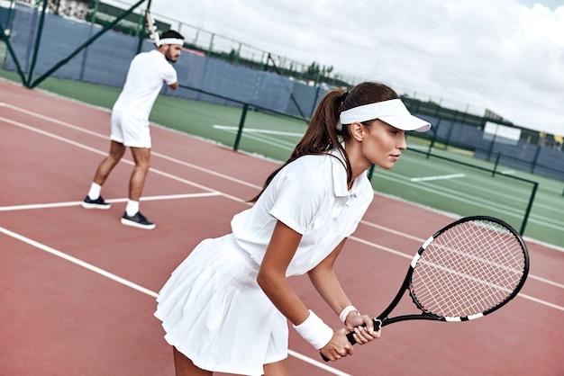 팀워크 아름다운 여자와 잘 생긴 남자가 테니스를 치고 있다