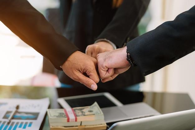 .3人の同僚のグループのチームワークビジネスコンセプトは、彼らの会議中に一緒に手を組みます。