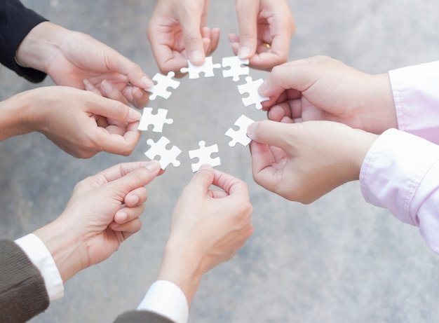 Teamwork of business people assembling jigsaw puzzle