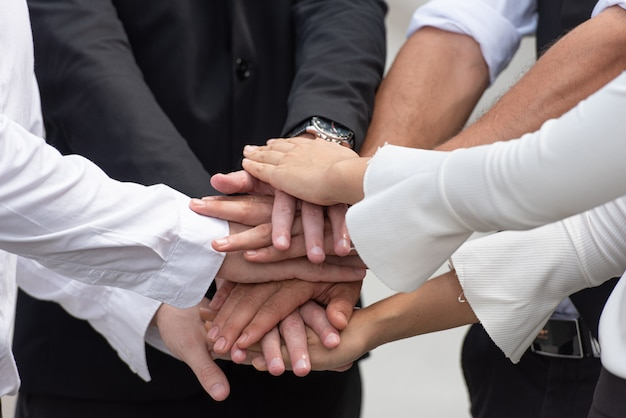 Teamwork of business people put hands together.