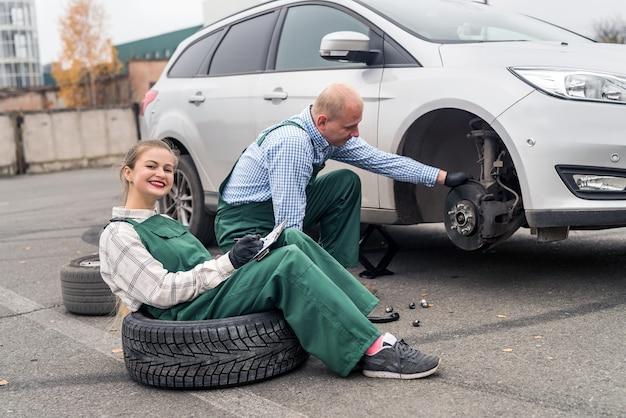 Teamwork on car service station, brake disk checking